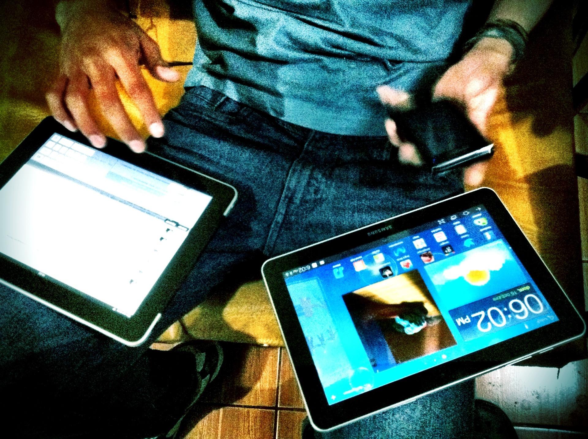 Un profesional maneja varios dispositivos digitales.
