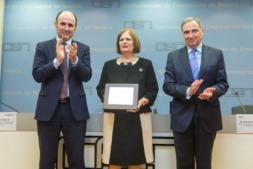María Teresa Garrido, escaltada por Manu Ayerdi y José Antonio Sarría, recibe el aplauso de los asistentes al acto.