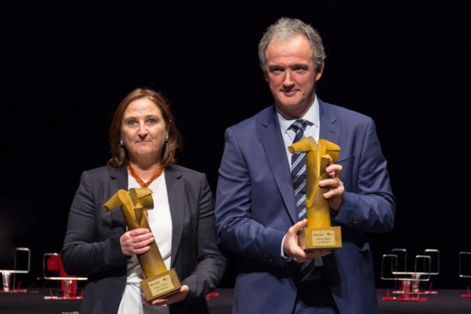 Maite Pellejero y Juanma Gorostiaga muestran los Premios a la excelencia concedidos al Instituto Cuatrovientos y a Mutua Navarra.