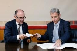 Manu Ayerdi y Mario Buisan intercambian los documentos durante la firma.