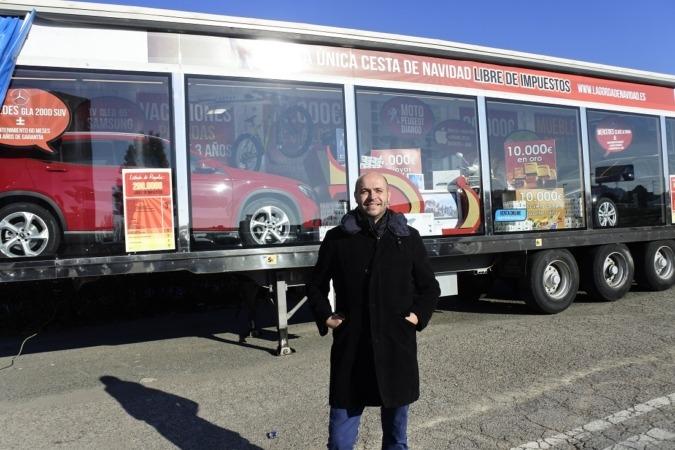 El responsable de Marketing de La Gorda de Navidad, Carlos Bóveda, junto al camión que expone los 200.000 euros en premios libres de impuestos.