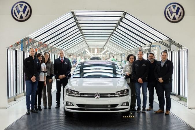 Foto de familia de los responsables del proyecto junto a uno de los vehículos Polo que se enviarán a Argelia.