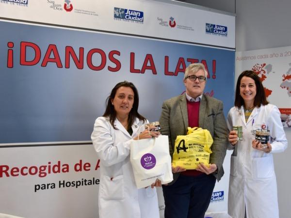 Tito Navarro, editor de NavarraCapital.es, entrega las latas recogidas entre los trabajadores de este medio a María Pilar Huarte, responsable de Voluntariado; y Elisa Molins, coordinadora de Cooperación Internacional.