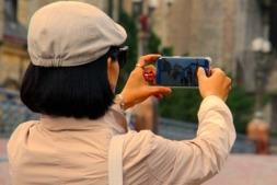 Una turista hace una fotografía con su smartphone.