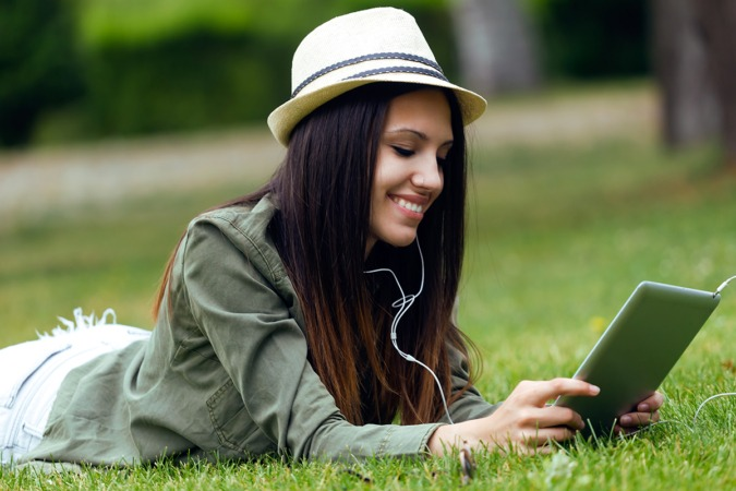 Portrait of beautiful young woman using digital tablet in the park.
