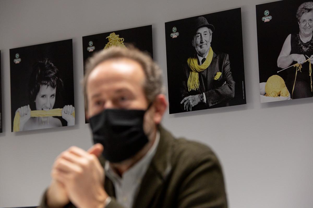 Santiago, padre de Daniel Palacio, ilustra uno de los cuadros que cuelgan en las oficinas de la empresa.